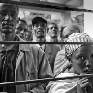 Ethiopian men rally around a woman, hoping a visiting physician will admit her to the hospital for treatment.