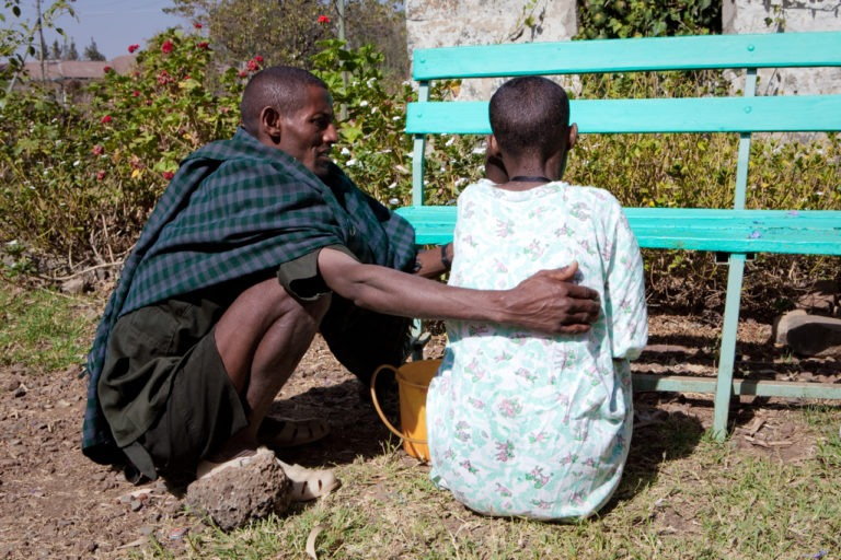 Man helping woman in Ethiopia