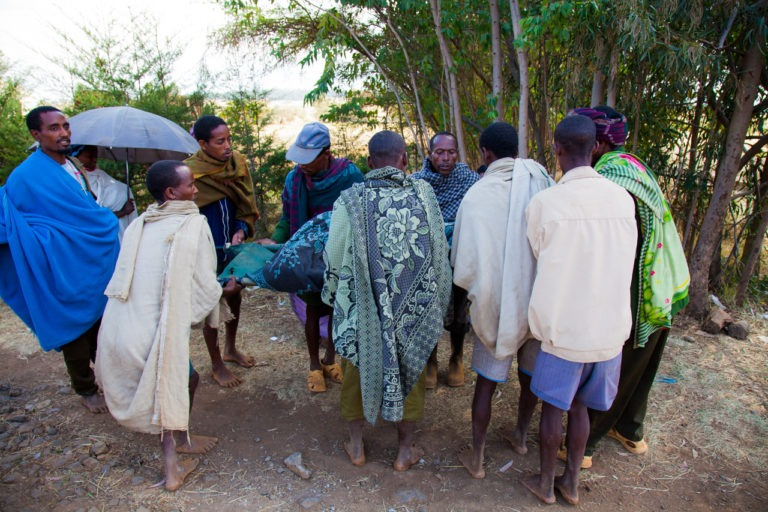 Men gather around a woman who has just had surgery to alleviate obstructed labor in preparation to carry her home. Motta, Ethiopia